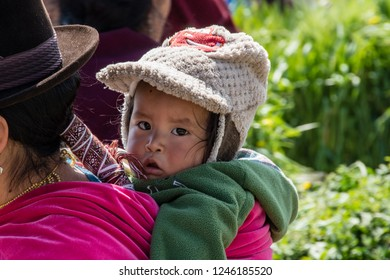 GUAMOTE, ECUADOR - OCT 18, 2018 : a child is carried on his mother's shoulders in the traditional Andean style, at the vegetable market of Guamote, near Riobamba on October 18, 2018.