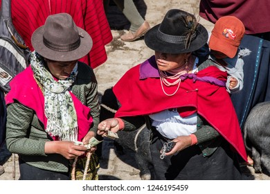 GUAMOTE, ECUADOR - OCT 18, 2018 : a woman pays the seller after buying a pig, at the weekly cattle market in Guamote near Riobamba on October 18, 2018.
