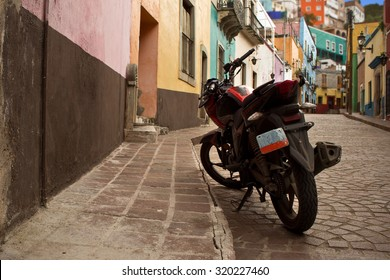 GUANAJUATO, MEXICO - September 24, 2015: Street view and a motorcycle in Guanajuato City, the UNESCO World Heritage Site. 16th century old buildings & streets are preserved.