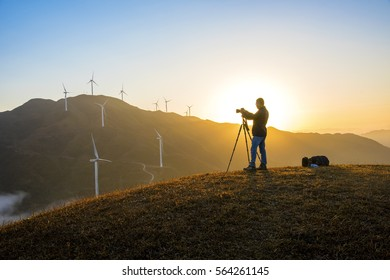 Guangdong, China, Nov. 23, 2016:Photographers in the mountain wind turbines and sunrise and sunset cloud background