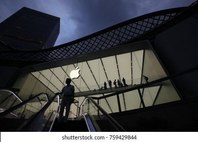 GUANGZHOU, CHINA - APR. 26. 2016: A man rides on escalator in front of the Apple store.