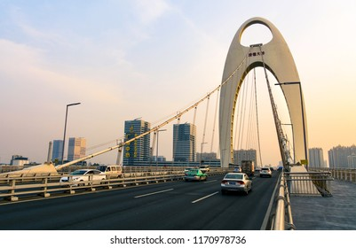GUANGZHOU, CHINA - JANUARY 3, 2018: Guangzhou Liede Bridge over Perl river with cars and pedestrian tracks at sunset
