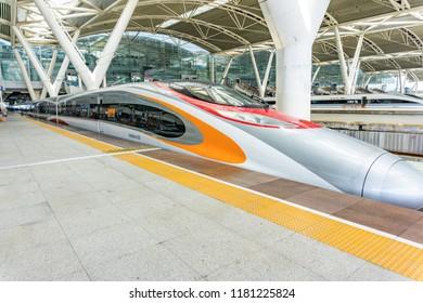 """Guangzhou, China - July 31, 2018: The MTR """"Donggan hao"""" of the Guangzhou-Shenzhen-Hong Kong Express Rail Link stops at Guangzhou South Railway Station."""