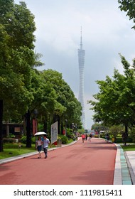 Guangzhou, China - June 09, 2018; People strolling in the gardens near the Canton Tower on a stormy day in  Guangzhou New Town.