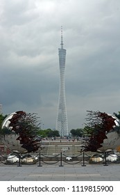 Guangzhou, China - June 09, 2018; Famous Canton Tower in the background with visitors and & Modern Sculpture in the foreground during a Summer storm.