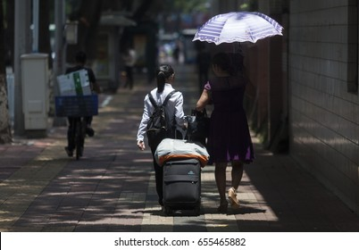 GUANGZHOU, CHINA - JUNE 7. 2017:Student leaving school with her mother after China's national college entrance examinations. Many parents of students in China are obsessed with so-called Gaokao exams.