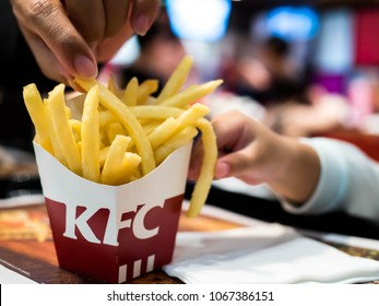 Guangzhou, China - MARCH 24,2018:  Woman and children hands Picking Kfc french fries on table, French fries, Happy family