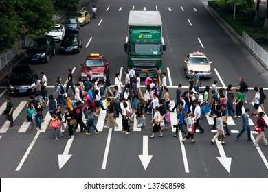 GUANGZHOU, CHINA  - MAY 2: Group of people crossing the street-upper view on May 2, 2013 in Guangzhou. China is the world's most populous country,Population over 1.3 billion.