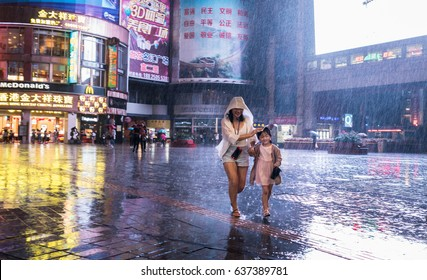 GUANGZHOU, CHINA - MAY 8. 2017 - People covers from the heavy rain while they walk on the street in Guangzhou, Guangdong province, China