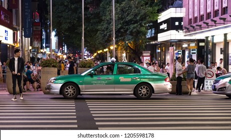 Guangzhou, China - October 10, 2018 : A local taxi cab waiting passengers at Beijing road pedestrian street, a shopping place along both side of the street with neon lights.