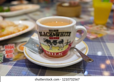 Guangzhou, China - October 10, 2018 : A ceramic cup of Black & White milk tea on the table. Black & White is a brand of Hong Kong-style milk tea.