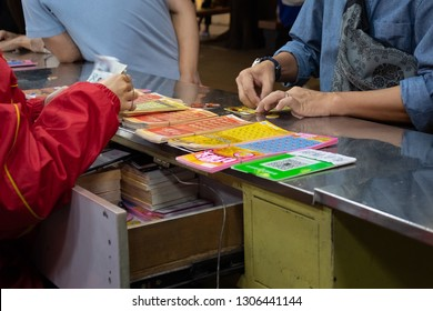 Guangzhou, China - October 10, 2018 : Hands scratching Chinese lottery ticket with coin.