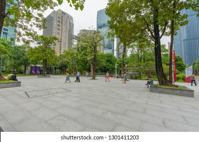 Guangzhou, China – October 24, 2018 : View of green tree and pond at Flower City Square with people walking and relaxing in Guangzhou, China on October 24, 2018.