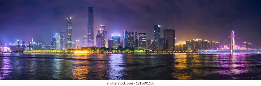 Guangzhou cityscape skyline over the Pearl River with Liede Bridge illuminated in the evening. Guangzhou, China