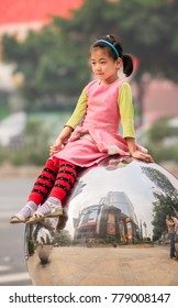 GUANGZHOU-DEC. 13, 2009. Adorable young girl on a chrome sphere. China has a traditional bias for sons. Many families abort female fetuses and abandon baby girls to ensure their one child is a son.