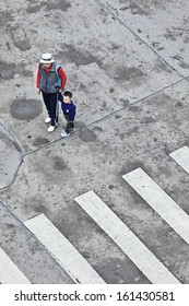 GUANGZHOU-FEB. 22. Grandmother guides five years old Ming Zhu on the street. Many young, hardworking Chinese couples leave their child in the care of their grandparents. Guangzhou, Feb. 22, 2012