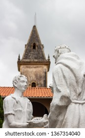 Guaramiranga, Ceará, Brazil. November 4, 2018:  Monastery of the Capuchins. White statues of priest and boy holding pigeon with church in the background. Interior of the Northeast of Brazil.