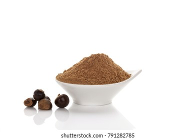 Guarana seeds and heap of guarana powder in white bowl isolated on white background.