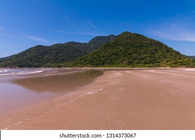 Guarau beach in Peruibe with a mountain and tropical forest in the background.