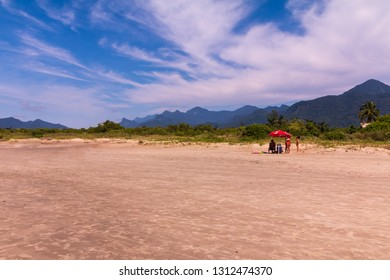 Guarau, Peruibe, SP / Brazil - 02/10/2019: Tourists in the tranquility in Guarau sand beach in Peruibe with the background of Jureia Ecological Station