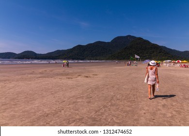 Guarau, Peruibe, SP / Brazil - 02/10/2019: Tourists in the tranquility of Guarau sand beach in Peruibe with the background of Jureia Ecological Station