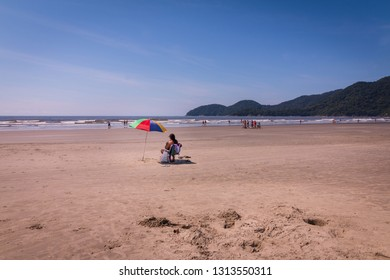 Guarau, Peruibe, SP / Brazil - 02/10/2019: Tourists in Guarau sand beach in Peruibe with the background of Jureia Ecological Station