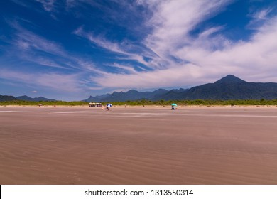 Guarau, Peruibe, SP / Brazil - 02/10/2019: Tourists walking in Guarau sand beach in Peruibe with the background of Jureia Ecological Station