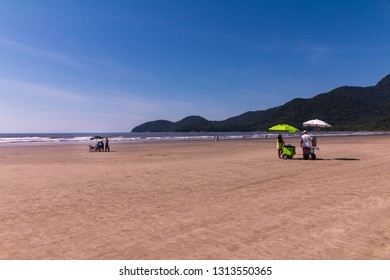 Guarau, Peruibe, SP / Brazil - 02/10/2019: Sallers in Guarau sand beach in Peruibe with the background of Jureia Ecological Station