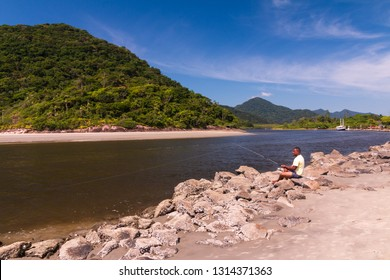 Guarau, Peruibe, SP / Brazil - 02/10/2019: Man fishing in the river with a mountain in background.