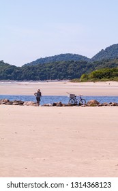 Guarau/Peruibe, SP / Brazil - 02/10/2019: Meadle age man fishing in the river with his biki at his side.