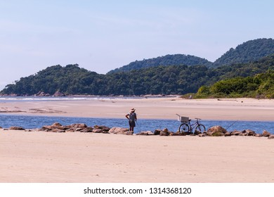 Guarau/Peruibe, SP / Brazil - 02/10/2019: Middle aged man fishing in the river with his biki at his side.