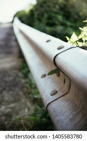 Guard railing with selective focus, asphalted road in Italy