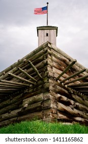 Guard Shack with the american flag on top of a vintage wooden wall with wood spikes protecting it.