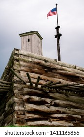 A guard shack on top of a wooden wall with wood spikes and a flagpole with the American Flag.