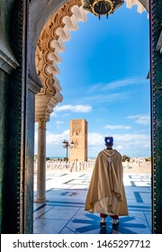 Guard soldier in national costume at the entrance of Mausoleum of Mohammed V and square with Hassan tower in Rabat on sunny day. Location: Rabat, Morocco, Africa