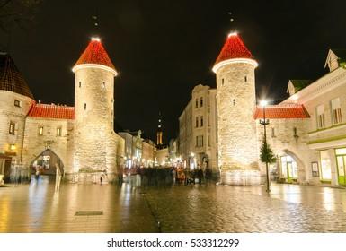 Guard towers of Viru Gate at Christmas, Narrow street illuminated of Old Town at night, City Hall on the background, Tallinn, Estonia