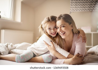 Guard your love. Mother daughter playing in bed.
