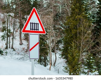 The guarded level crossing is 50-100 meters ahead. Guarded level crossing sign, snowy forest in the background.