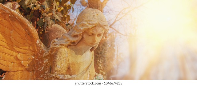 Guardian angel. Ancient stone statue in sunlight. Copy space for design.