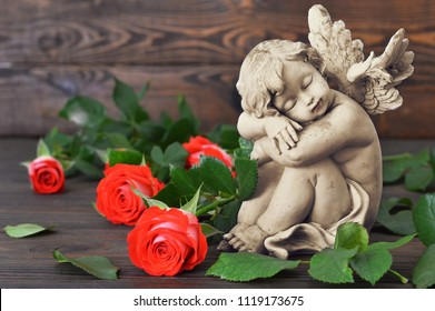 Guardian angel and roses on wooden background