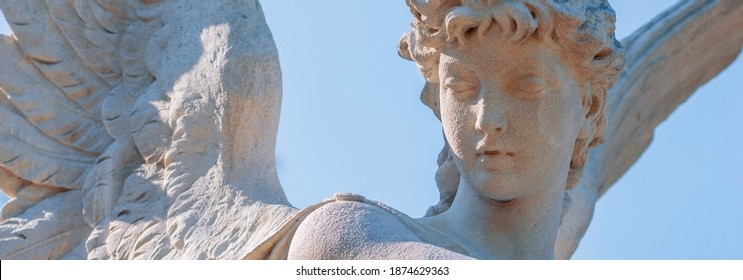 Guardian angel statue in light as a symbol of strength, truth and faith. Horizontal image.