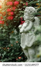 Guardian angel statue in sunlight as a symbol of love in garden