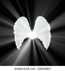 Guardian Angel   white wings over black background with light. Religion and spiritual concept