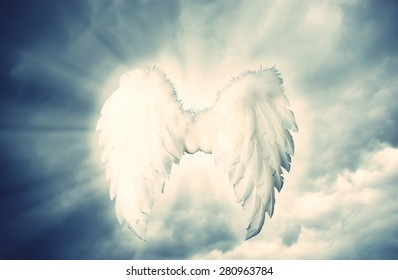 Guardian Angel white wings over dramatic grey with light. Religion and spiritual concept