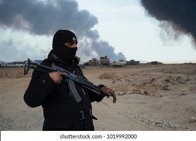 A guardian with his AK47 to protect the access of an oil well set on fire by ISIS to slow down the coalition's advance.