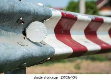 guardrail with red stripes along the road with a white reflector
