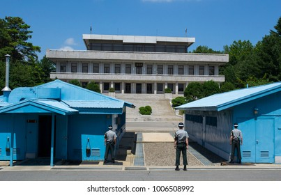 Guards looking across the border in the demilitarized zone (DMZ) between North Korea and South Korea, with the blue special meeting huts either side