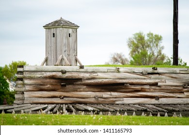 A guardshack on top of a wooden wall with wood spikes at Fort Stanwix, New York