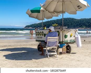 Guaruja, São Paulo, Brazil. April 2015. Vendor sells fresh coconut water (juice) and boiled corn on a beach.