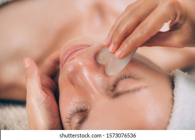 Guasha face massage with jade stone. Close-up of a young woman's face